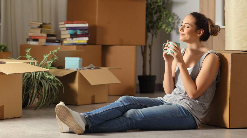 Une jeune femme heureuse d'avoir emménagé dans son logement neuf